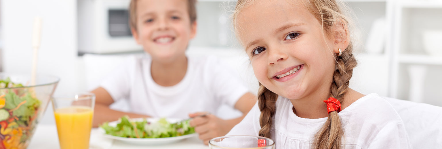 Two kids are sitting in dining table